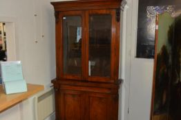 A mid-Victorian rosewood bookcase cabinet, the upper section with moulded cornice above a pair of