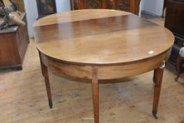 A George III mahogany three part dining table of a pair of demi-lune tables, one with hinged drop