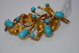An Iranian gold and turquoise brooch, modelled as a leaf spray, set with turquoise cabochons and