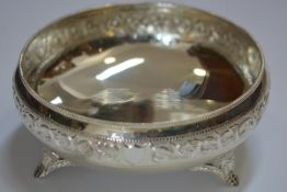 An Indian silver footed bowl, chased with a foliate scroll rim and raised on splayed feet,