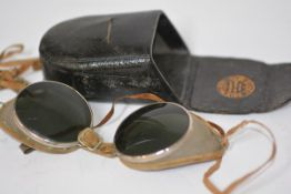 A pair of 1930's motorcycle goggles, in white metal with tinted lenses and mesh sides, in a fitted