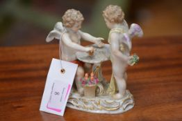 A Meissen figure group, c. 1900, of two putti playing dice at a table, a basket of flowers at