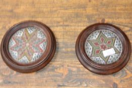 A pair of mid-Victorian beadwork, mahogany framed table coasters or stands, each of circular form,