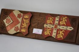 An oak book slide painted to each end with the crests of Cambridge University and Trinity College,