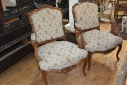 A pair of Louis XV style walnut framed fauteuils, each with leaf and scroll carved crest rail, the