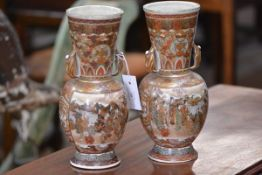 A pair of Meiji period Satsuma twin-handled vases, each with elongated tapering neck, foliate