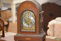 An early 20th century inlaid mahogany bracket clock, the arched case enclosing a conforming gilt