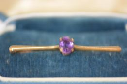 A 9ct gold bar brooch set with an oval-cut amethyst, cased. Length 54mm,