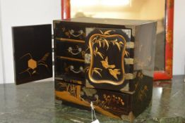 A Japanese black and gilt lacquer table cabinet, early 20th century, the top decorated with an image