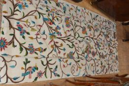 A pair of crewel work curtains, worked with birds amidst flowering boughs in coloured wools