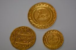 Three yellow metal coins, one Islamic, probably Indian (Mughal?); together with two engraved with