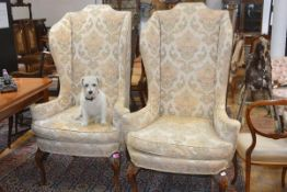 A pair of walnut-framed high back wing chairs in the Queen Anne taste, early 20th century, each with
