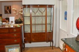 An early 20th century inlaid mahogany vitrine cabinet, of serpentine outline, with moulded cornice