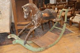 A 19th century carved and painted rocking horse, possibly G. & J. Lines, with boldly scrolled bow