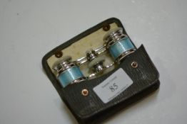 A pair of sky blue engine turned enamel and mother of pearl opera glasses, mounted in white metal,