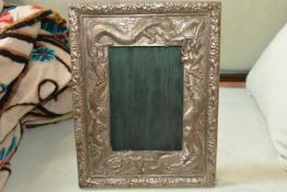 A Chinese white metal photograph frame, chased in relief with dragons and fruit and foliage (a/f,