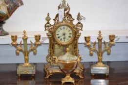 A gilt-metal mounted onyx clock garniture, the drumhead clock with Roman numerals within a case
