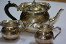 An Indian silver three piece tea service, 20th century, each piece of spherical form, the teapot