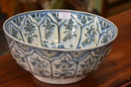 A large Islamic blue and white pottery bowl, 17th/18th century, painted to the well with a flower