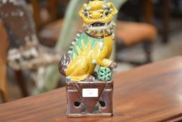 A Chinese earthenware model of a dog of fo, glazed in yellow, green and brown. 29cm