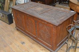 A carved oak coffer in 17th century style, c. 1900, the triple panelled top carved in relief with
