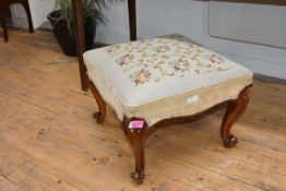 A 19th century walnut-framed footstool, the square needlework seat raised on cabriole legs with