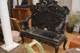 A striking Japanese carved hardwood settee, c. 1900, the high back pierced and carved in high relief