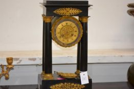 A French Empire ebonised and gilt-metal portico clock, the gilt chapter ring with Roman numerals