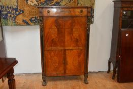 An early 19th century marquetry inlaid walnut secretaire abattant in the Egyptian Revival taste, the