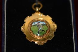 A 9ct gold and enamel Rugby Union medal, decorated with a running figure in coloured enamels, the