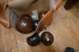 A set of four lignum vitae lawn bowls; together with two Thomas Taylor bowls, in a carrying case (