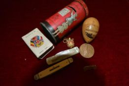 A group including a tin pillar box money bank, Mauchline type egg sewing kit; World War I