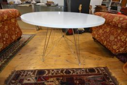 A modernist white polymer circular dining table with chrome base