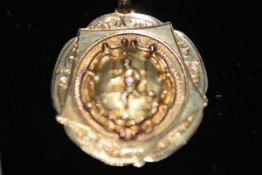 """A 9ct gold Rugby Union medal, chased with the figure of a player, the reverse engraved """"M.R.F.C. ("""