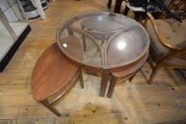 A Nathan vintage glass topped teak coffee table, of circular form, the shaped stretchers enclosing