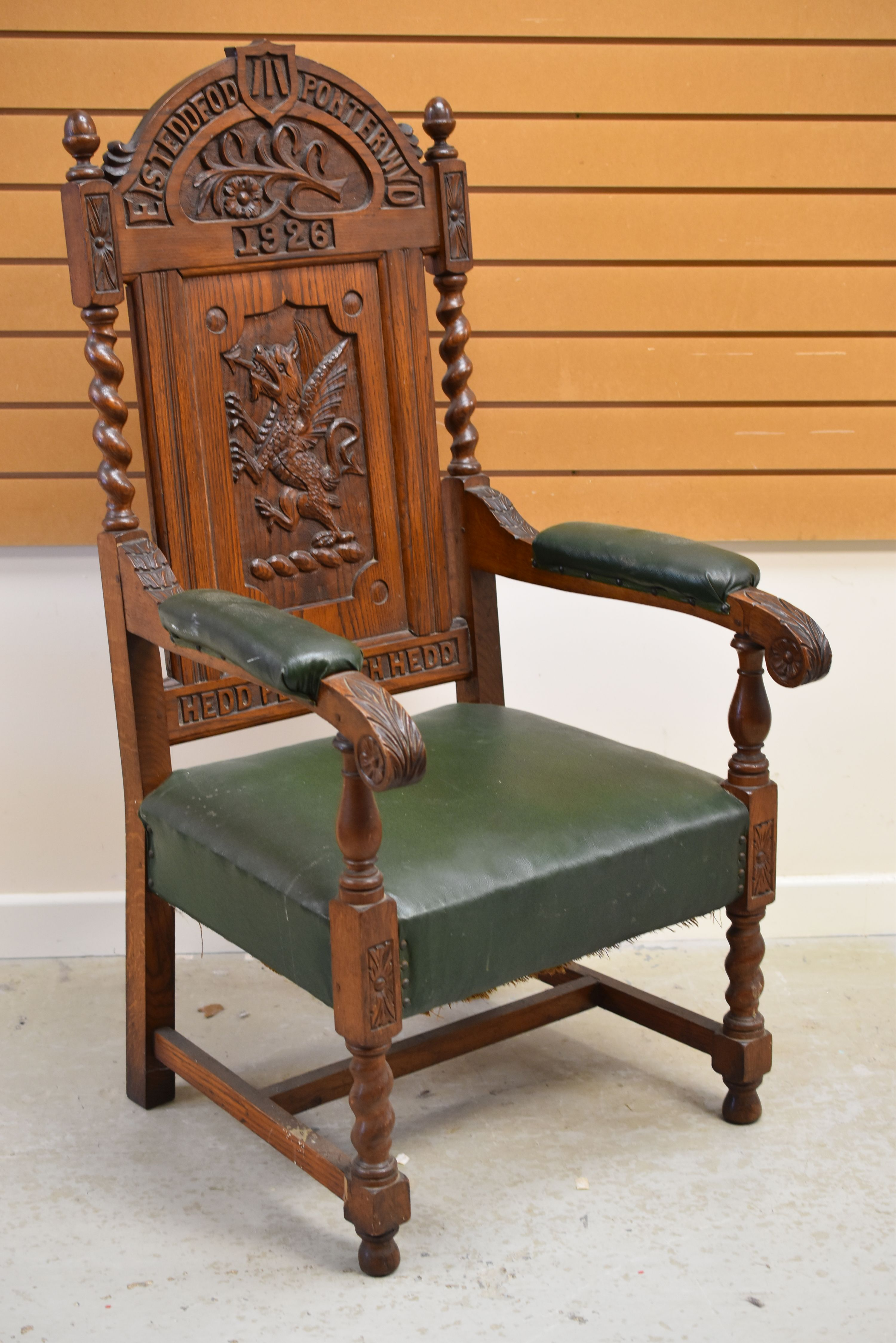 A WELSH EISTEDDFOD CHAIR carved with a dragon to the back and with leek and daffodil above,