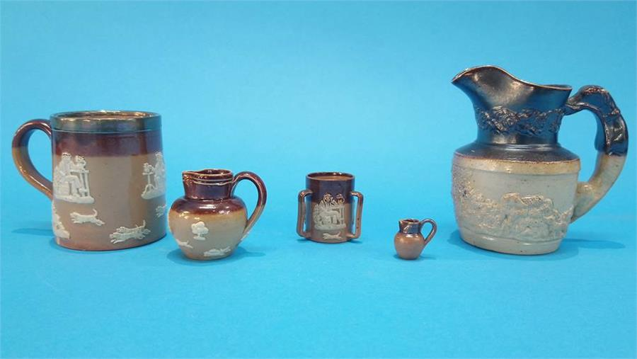 Lot 39 - A stoneware jug with dog looped handle and four pieces of Doulton stoneware. (5)