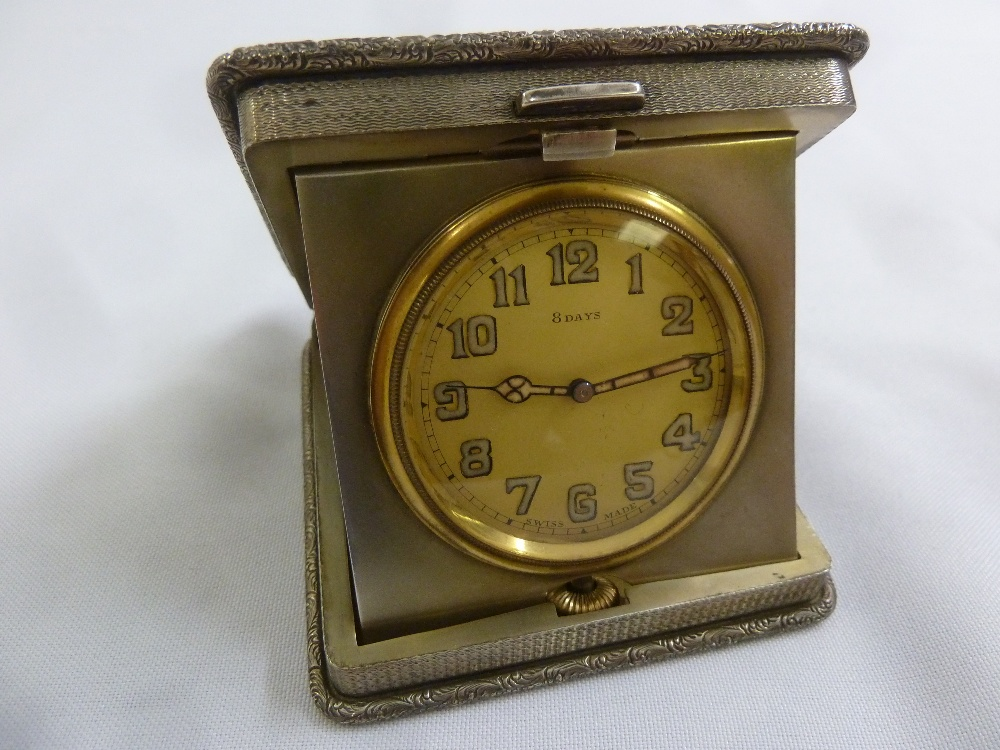 Lot 352 - A silver engine turned 8 day travel clock shaped square with bar push clasp to hinged cover,