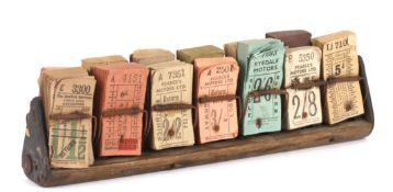 A collection of various coloured bus tickets in wooden stand. Dating from post-war, no later than