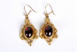 A pair of Victorian style cabochon garnet set drop earrings the central oval garnets within