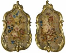 A pair of early 19th Century gilt framed chenille work panels of floral design in ornate gilt wood