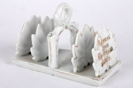 A porcelain toast rack 'A Present from The Crystal Palace' modelled as leaves highlighted in gilt
