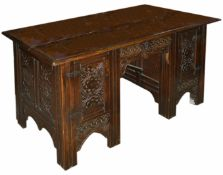 An oak carved knee hole desk, late 19th century of rectangular form with central drawer flanked by