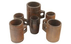 Four assorted wooden measures, late 19th century and later each with finger hole handle and with a