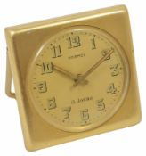 A 1950s gilt metal 8-day travel clock by Hermes with easel stand, and dial with Arabic numerals,