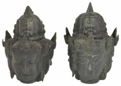 A pair of antique three sided bronze heads, possibly Tibetan the female heads with spiked helmets