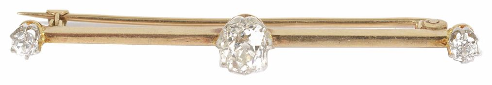 An Edwardian diamond set bar brooch with an oval old cut diamond to centre, flanked by single