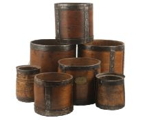 A collection of seven 19th and early 20th century wooden grain measures, each with metal banding,