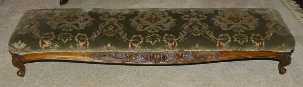 A Victorian mahogany footstool, of long proportions with upholstered upper section above foliate