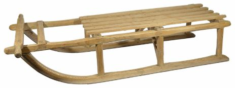 A vintage pine sledge with slatted seat upon turned supports with metal runners width 26.5 x 117 x
